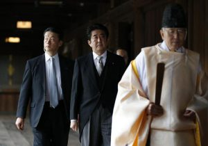 623811-japan-s-pm-abe-is-led-by-a-shinto-priest-as-he-visits-yasukuni-shrine-in-tokyo