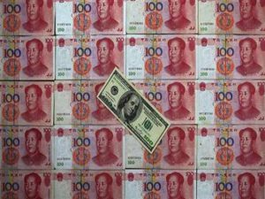 A U.S. $100 banknote is placed on top of 100 yuan banknotes in this picture illustration taken in Beijing