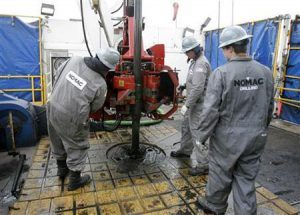 Workers change drilling pipes on the rotary table of a natural gas drilling rig near Towanda Pennsylvania