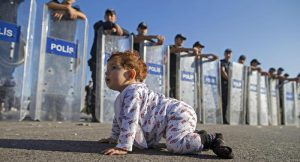 epa04937946 A Syrian refugee baby plays in front of riot police at the Istanbul-Edirne highway as they wait for permission to pass Turkish Greek border to reach Germany in Edirne, Turkey 19 September 2015. Turkey has spent 7.6 billion US dollar on caring for 2.2 million Syrian refugees since the civil war began in 2011, Deputy Prime Minister Numan Kurtulmus said on 18 September. Turkey hosts more Syrians who fled their homeland than any other country. Most Syrians, however, have no legal right to work and rights groups report housing remains a huge issue for many. EPA/TOLGA BOZOGLU EPA/TOLGA BOZOGLU