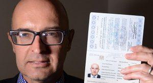 Il reporter inglese Nick Fagge con il passaporto (originale) che ha acquistato in Turchia per meno di 2mila euro.