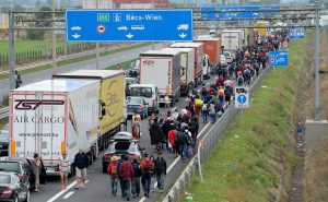 epaselect epa04914186 Large numbers of refugees walk along a lane of the M1 motorway near to Nickelsdorf, on the Austria-Hungarian border 5 September 2015. The first of thousands of refugees reached Austria early 5th Sept after busloads left Hungary in a mass exodus after the Austrian and German governments agreed to receive them. EPA/ROLAND SCHLAGER
