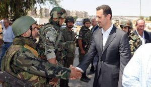 Syrian President Bashar al-Assad (C) shakes hands with a Syrian army soldier in Daraya, southwestern of the capital Damascus on August 1, 2013.
