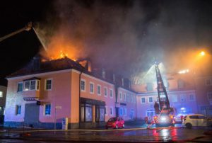 epa05173402 Fire fighters extinguish flames at a former hotel in Bautzen, Germany, where a fire broke out overnight 21 February 2016. The cause of the fire is yet not determined but authorities were investigating 'into all directions', police said. The former hotel was planned to be used as an accomodation for refugees. Reportedly the work of the fire brigade was massively hindered by a few, mostly boozed, onlookers.  EPA/RICO LOEB