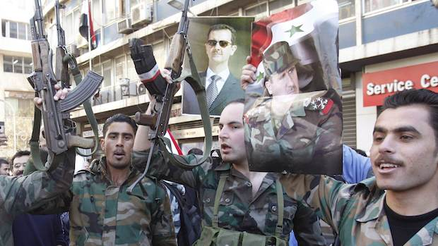 Soldiers from forces loyal to Syria's  President Bashar al-Assad attend a rally supporting him and the army in Damascus
