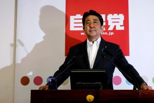 Japan's PM and leader of the ruling LDP Abe poses for photos before a news conference following a victory in upper house elections by his ruling coalition in Tokyo