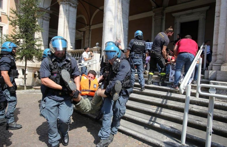 manifestanti portati via di peso