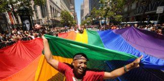 Persona di colore che tiene bandiera arcobaleno