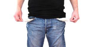 Persona che mostra le tasche dei pantaloni vuote, sinonimo di povertà