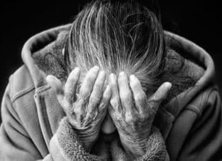 anziana che si copre viso in bianco e nero