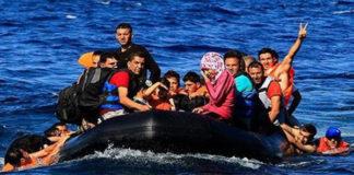 immigrati salutano da un gommone in mezzo al mare