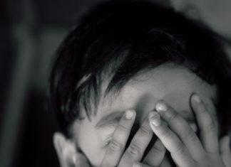 bambino con mani sulla faccia