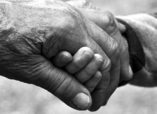 mano di anziano e mano di bambino