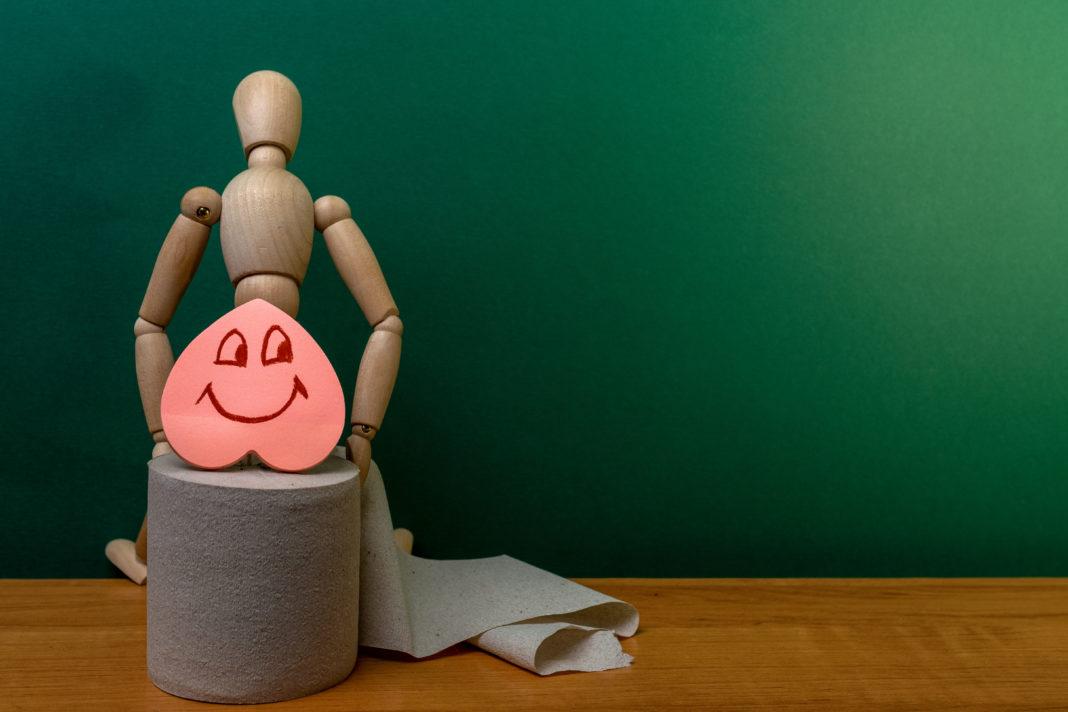 burattino seduto su un rotolo di carta igienica, con un sapone a forma di cuore come appoggio lombare