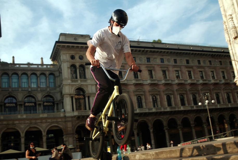 globalista distanziato in bici a milano
