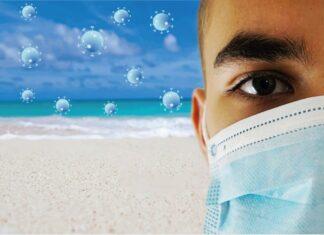 uomo con mascherina anti coronavirus in spiaggia